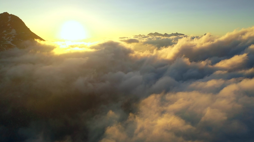 Aerial, reverse, drone shot, over clouds at sunrise, near Jungfrau region and the Aletsch glacier, on a sunny, summer morning, in the Swiss alps of Valais, Switzerland #1036207766
