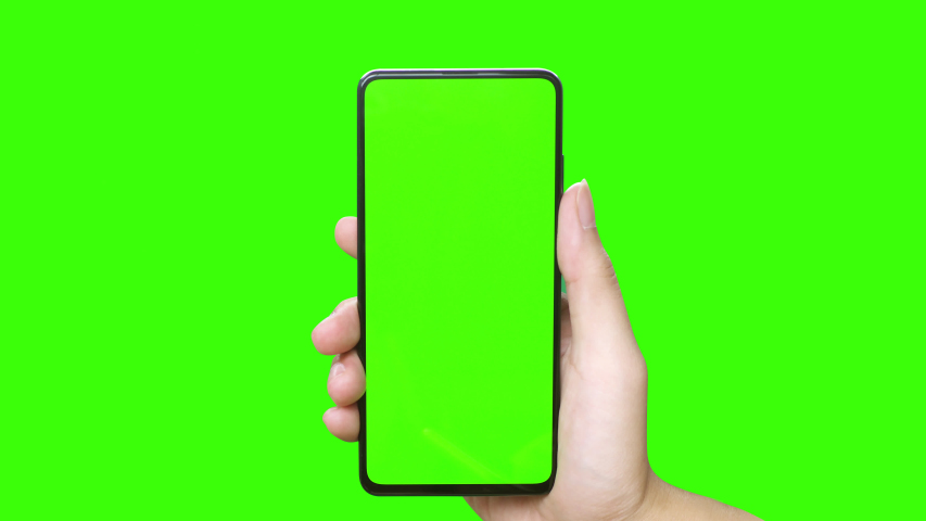 Man's hand holding a mobile telephone with a vertical green screen in tram chroma key smartphone technology cell phone touch message display hand with luma white and black key