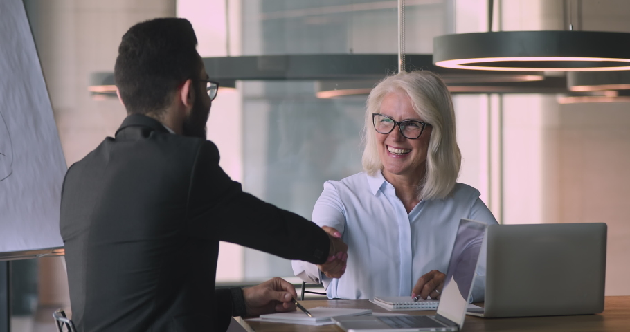 Happy middle aged mature caucasian businesswoman and young arabic arab businessman talking negotiating handshaking at office business meeting make commercial partnership agreement deal concept | Shutterstock HD Video #1036280456