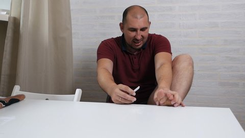 A man pedicures himself at home with a silly, funny expression on his face