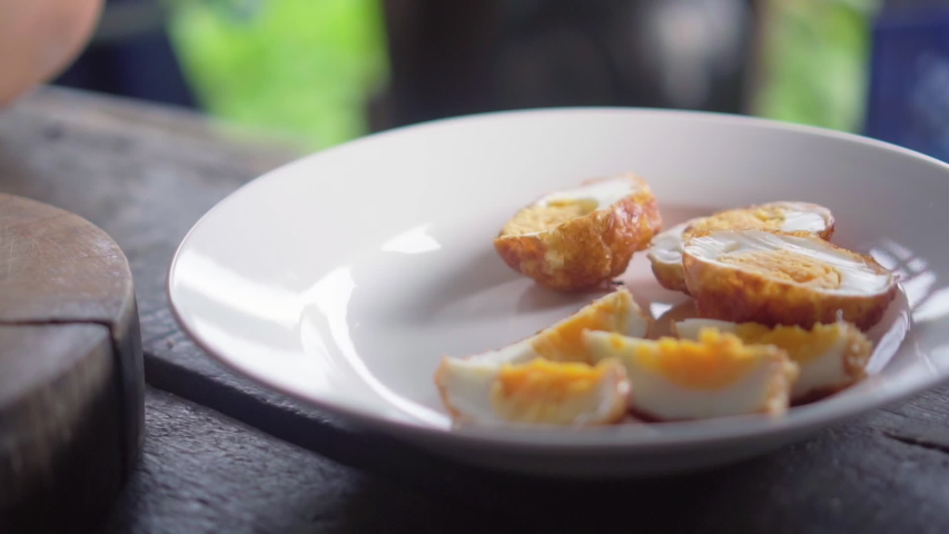 Fried boiled egg with tamarind sauce get decorated on dish. Slow motion. | Shutterstock HD Video #1036349096