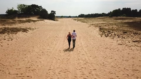 Veluwe / Netherlands - 08 26 2017: Veluwe, Netherlands, 08/26/2017, Forward drone shot of two young people walking in the Veluwe, Netherlands, on a bright sunny day