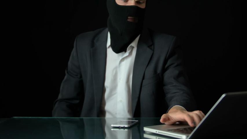 Gun-man in balaclava using computer, preparing for attack, blackmail crime | Shutterstock HD Video #1036369316
