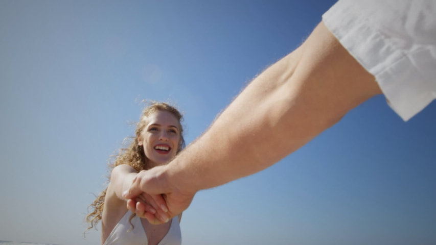 Animation of a young Caucasian woman walking on a beach holding hand of her partner, seen on a screen of a smartphone in picture mode with icons in the foreground | Shutterstock HD Video #1036412186