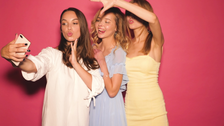 Three young smiling hipster women in summer dresses.Girls taking selfie self portrait photos or video on smartphone.Models posing in the studio near pink wall.Making duck face,show positive grimace | Shutterstock HD Video #1036476506