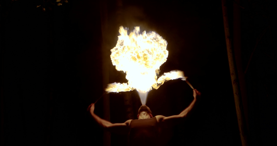 Fire breathing man is waving two burning torches in darkness | Shutterstock HD Video #1036500416