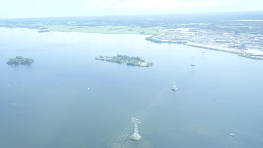 An aerial view of a lake in Europe, The Netherlands with green nature, an island, cell tower masts and a town in the frame. The clip is in fifty frames per second out of an airplane.   Shutterstock HD Video #1036510856