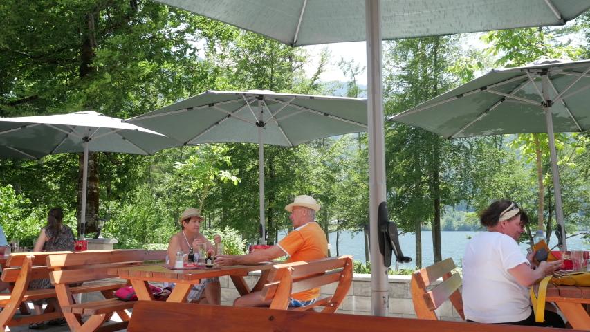 Grundlsee, Styria, Austria - July 2019. People dining at Gasthaus Murbodenhüttl overlooking Grundlsee lake. Grundlsee, Ausseerland - Salzkammergut lakes region and Dead Mountains, Liezen, Styria   Shutterstock HD Video #1036535186
