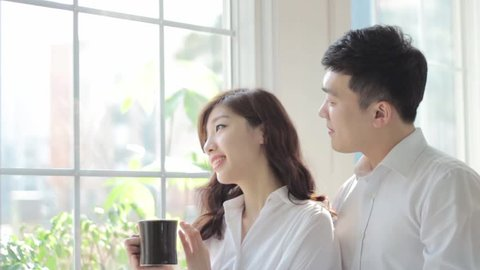 beautiful young couple having a pleasant conversation over coffee while looking out a window in a bright room