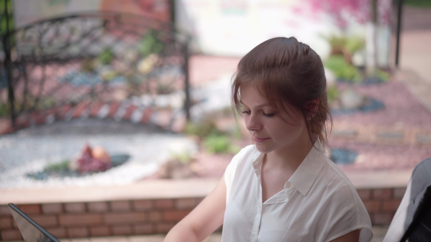 Young businesswoman in a street cafe is typing on a laptop. | Shutterstock HD Video #1036669196