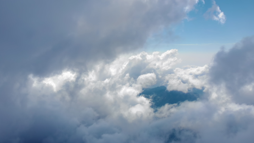 Flying through beautiful thick fluffy clouds. Amazing timelapse of soft white clouds moving slowly on the clear blue sky in pure daylight. Direct view from the cockpit. | Shutterstock HD Video #1036992296
