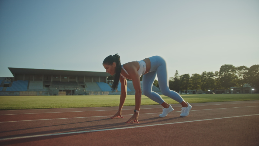 Beautiful Fitness Woman in Light Blue Athletic Top and Leggings is Starting a Sprint Run in an Outdoor Stadium. She is Running on a Warm Summer Day. Athlete Doing Her Sports Practice. | Shutterstock HD Video #1037027396