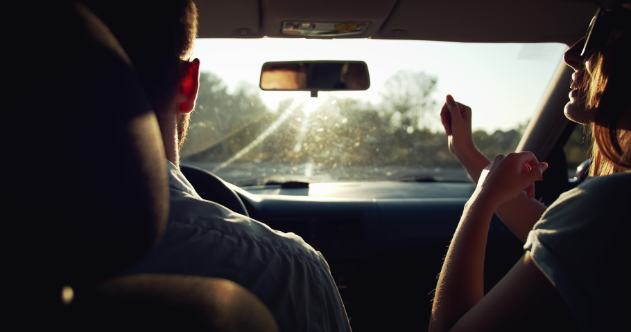 Cheerful boyfriend and girlfriend having fun and kissing in car, couple in love travelling | Shutterstock HD Video #1037050706