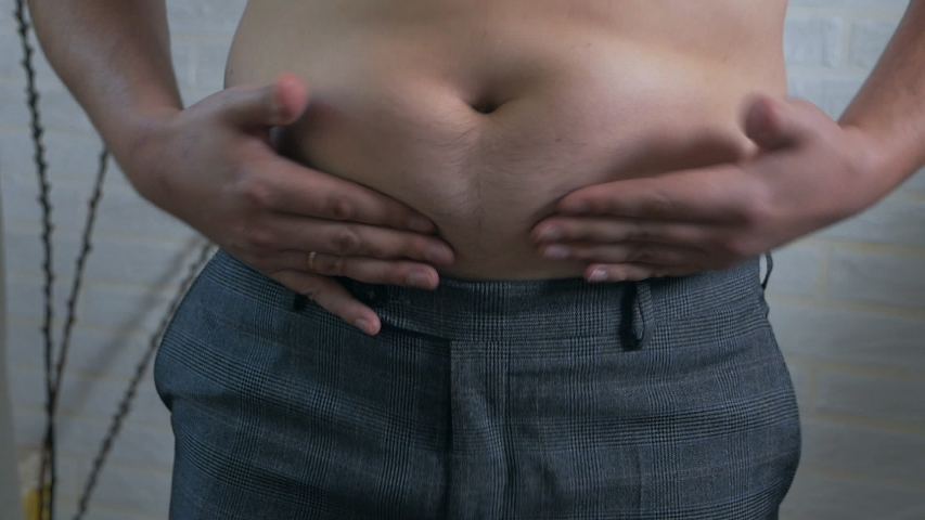 Close-up, male stomach, overweight. Young man with a naked fat belly shakes fat folds on his stomach, obesity, health, beer belly | Shutterstock HD Video #1037144306