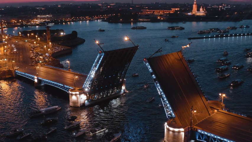 White night in St. Petersburg: Amazing drone view of Neva River with opened Palace Bridge and many tourist boats nearby, in the background sunset sky above Peter and Paul Fortress | Shutterstock HD Video #1037163506