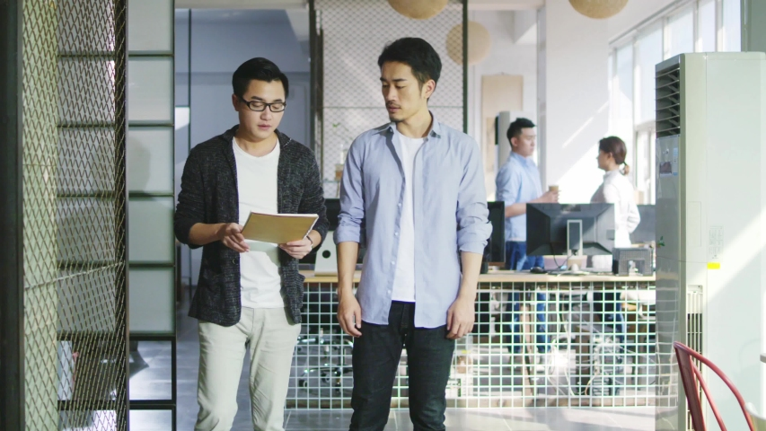 Two young asian office worker discussing business while walking in company | Shutterstock HD Video #1037186486