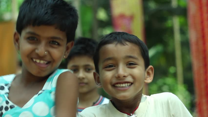 Happy kids in a village in India laughing and smiling together. Narrow depth of field.