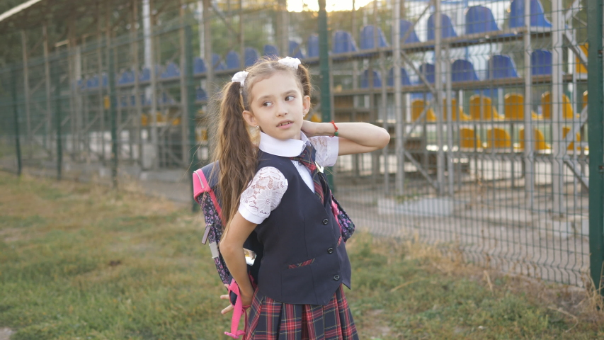 Student elementary school wears a backpack on his shoulders and goes home from school. | Shutterstock HD Video #1037198786
