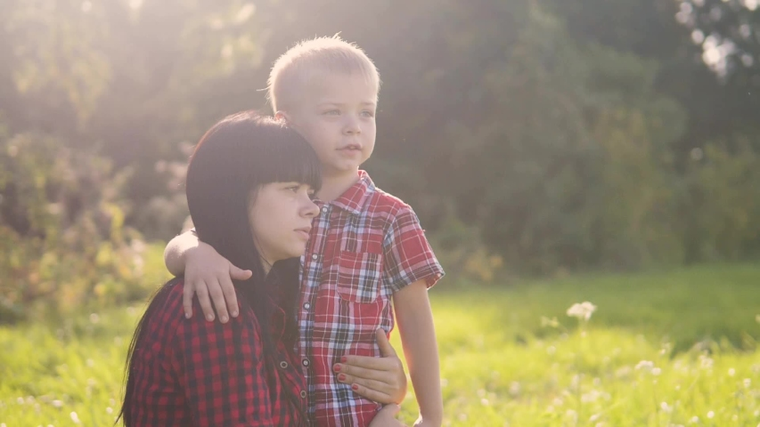 Happyfamily mother's day the nature slow motion video teamwork outdoors . son boy hugs mom girl outdoors shows the lifestyle distance with his hand sunlight cute video care. mother and son cuddle   Shutterstock HD Video #1037217926