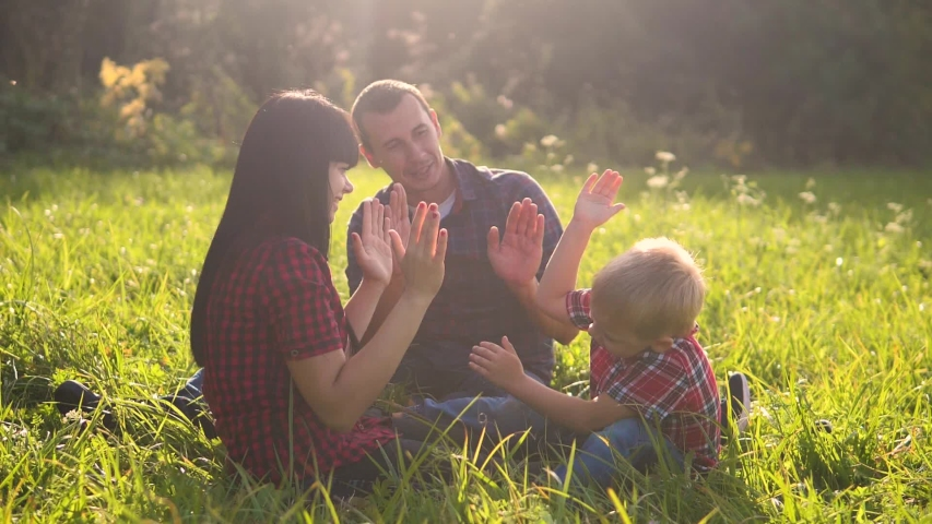 Happy family teamwork outdoors concept outdoors slow motion video. mom lifestyle dad a and son in nature are sitting on the grass have fun. playing mom girl dad man and son boy happy family   Shutterstock HD Video #1037218016