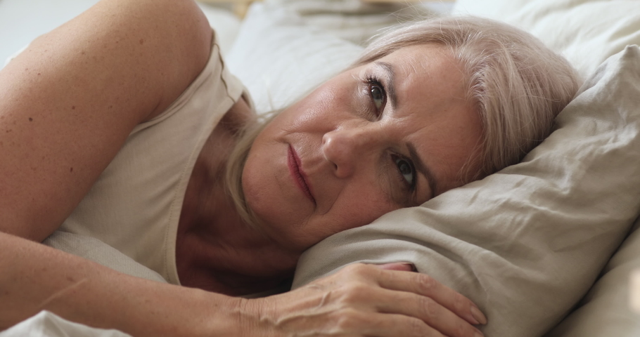 Annoyed middle aged mature woman feel frustrated suffer from insomnia uncomfortable bad mattress lying awake in bed, upset senior old lady insomniac trying to sleep disturbed toss and turn in bedroom | Shutterstock HD Video #1037252546
