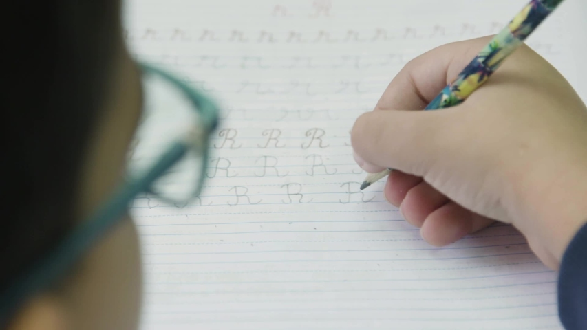 Over the shoulder shot of a boy wearing glasses, learning to write at school | Shutterstock HD Video #1037254766