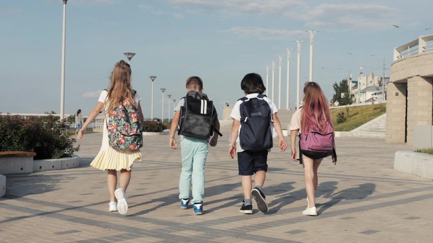 School kids walking with backpacks. | Shutterstock HD Video #1037264036