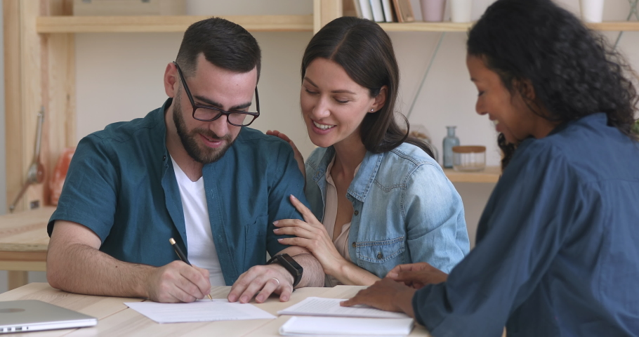 Happy excited young family couple customers clients sign mortgage investment contract sale purchase agreement deal handshake insurer agent take bank loan buy insurance service meeting broker realtor | Shutterstock HD Video #1037298266