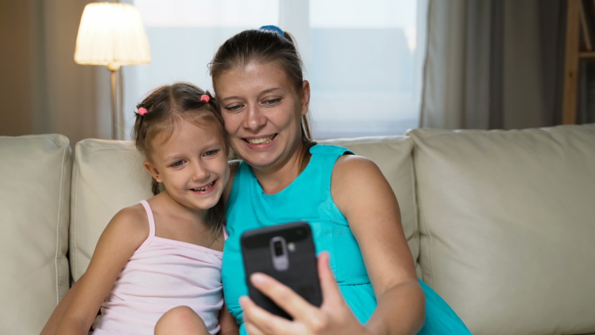 Little Girl Child With Mother Home On Sofa Using Smartphone   Shutterstock HD Video #1037314496