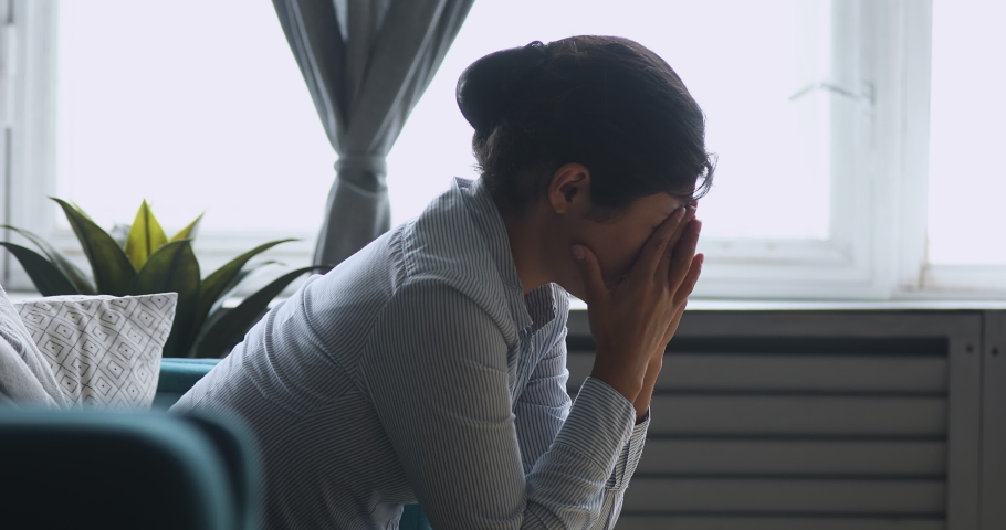 Depressed worried sad indian girl sit alone at home concerned about problem, upset desperate young woman feeling weak frustrated lonely jealous anxious regret mistake or abortion concept, side view | Shutterstock HD Video #1037352896