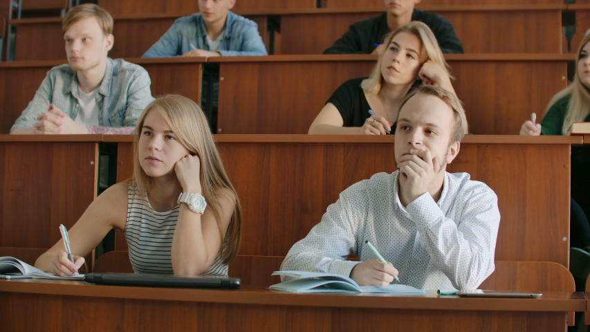 In the Classroom Multi Ethnic Students Listening to a Lecturer and Writing in Notebooks. Smart Young People Study at the College | Shutterstock HD Video #1037361236