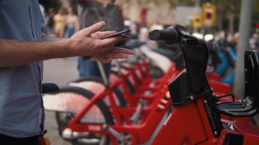 Tourist man take Electric Kick scooter or bike bicycle in sharing parking lot, tourist phone application. New sharing business project started in city, eco transportation
