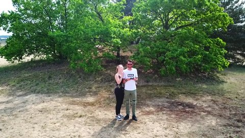 Veluwe / Netherlands - 08 26 2017: Veluwe, Netherlands, 08/26/2017, Rising drone shot of two young people near a tree in the Veluwe, Netherlands, on a bright sunny day
