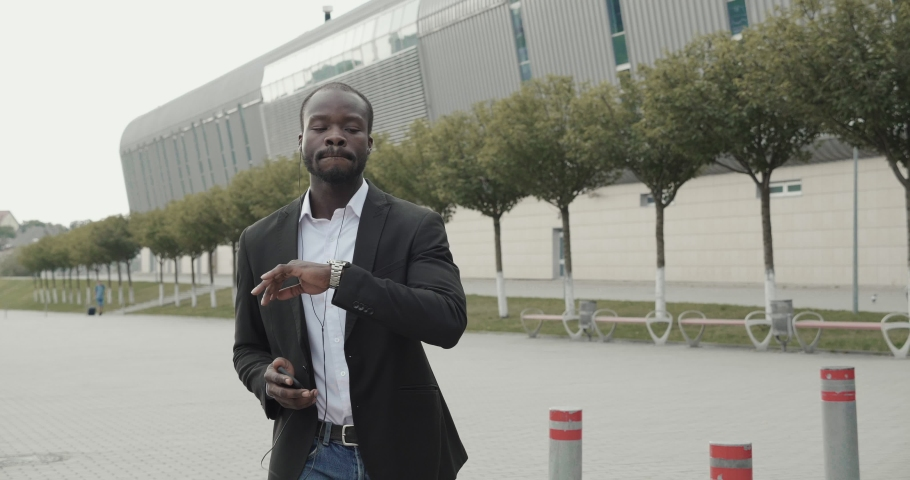 Young Male Businessman dancing in fashionable Black Jacket. Enjoying his time outside Office. Beautiful summer evening. Afro American listening to Music with Headphones. Slow Motion. | Shutterstock HD Video #1037444216