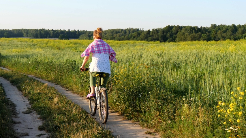 A young European girl rides a bicycle through a summer green field, wearing green trousers, a pink checked shirt and sunglasses, and smiles. Cycling, outdoor activities. Sports recreation. | Shutterstock HD Video #1037507336