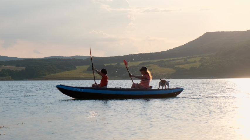 Happy mother and son, dog rowing on an inflatable kayak on water of a large lake on a background of picturesque cliffs and green vegetation, a beautiful sunset of the day. Family sports. Lifestyle | Shutterstock HD Video #1037558936