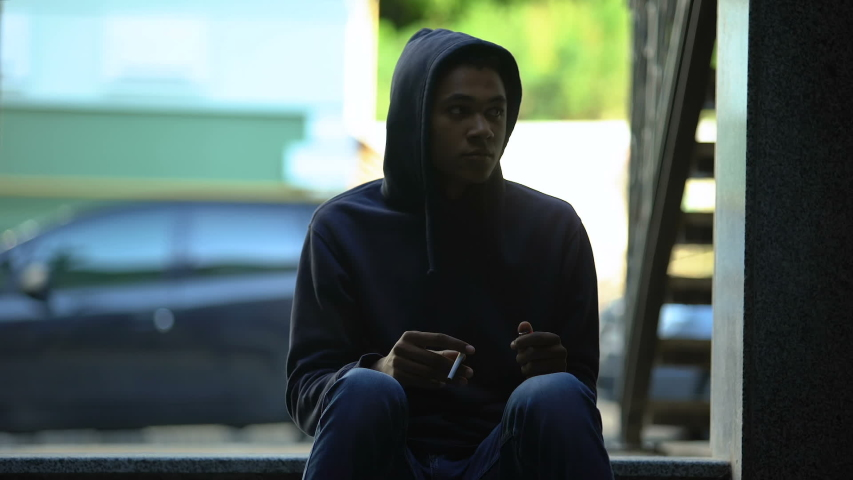 African american teenager cautiously looking around, hiding to smoke cigarette | Shutterstock HD Video #1037744906