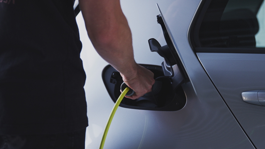 Close Up Of Hand Attaching Power Cable To Environmentally Friendly Zero Emission Electric Car | Shutterstock HD Video #1037784146