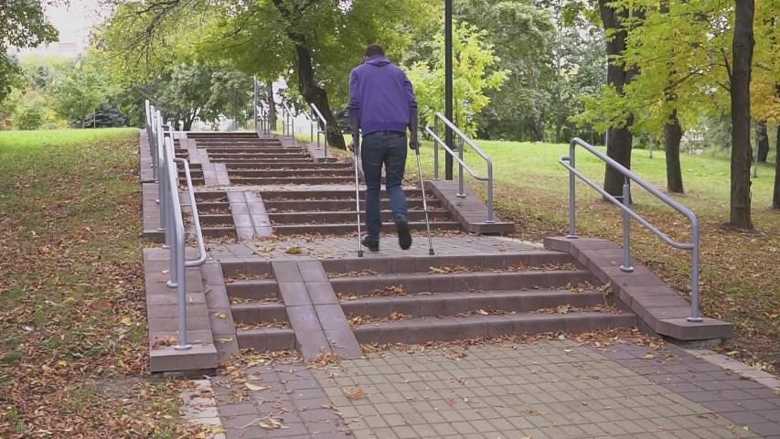 Man on crutches climbs a set of stairs. Concept on an inclusive society and a barrier-free environment