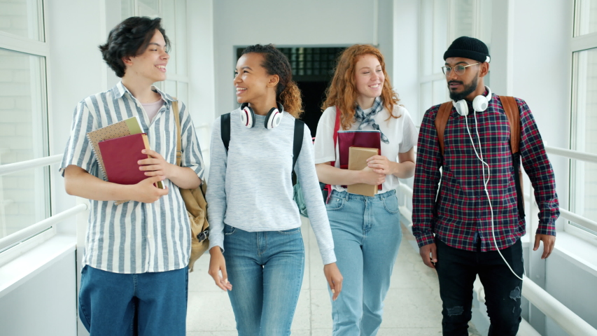 Cheerful students multi-racial group are talking walking with books in college hall showing thumbs-up laughing. Emotions, lifestyle and education concept. | Shutterstock HD Video #1037842556