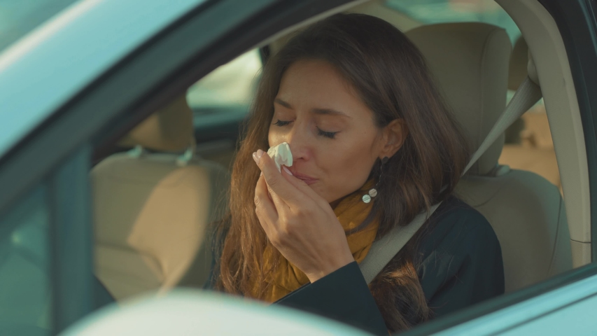 Young woman sitting in car feesneeze holds a handkerchief sick seat belt fastens vehicle influenza health illness flu medical sickness problem business infection headache slow motion