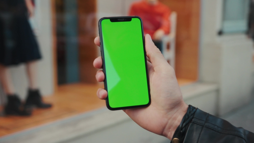 NEW YORK - April 5, 2018: Young man hands holding a smartphone with vertical green screen background car people city touchscreen wireless business evening cellphone communication device digital | Shutterstock HD Video #1037971646