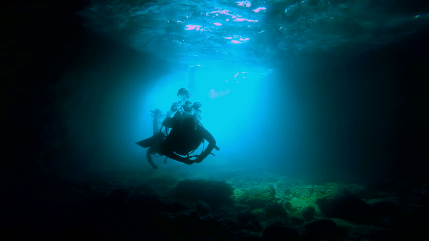 Two silhouettes of Scuba Divers swimming,with sun rays in a cave.  | Shutterstock HD Video #10382555