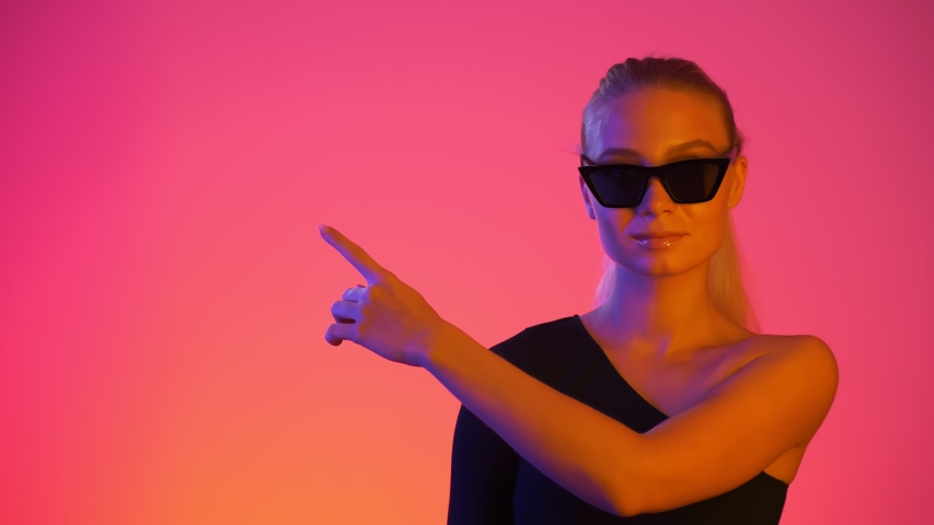 Beautiful young girl in sunglasses makes gesture pointing finger away at free space of frame. Neon light and vivid red and blue colors isolated over red gradient background | Shutterstock HD Video #1038289316