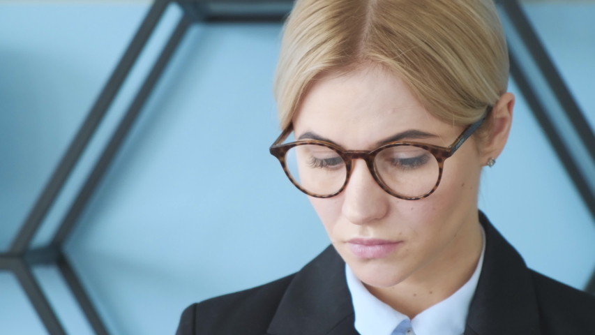 The face of a beautiful blonde girl with glasses: she reads the documents. | Shutterstock HD Video #1038298436