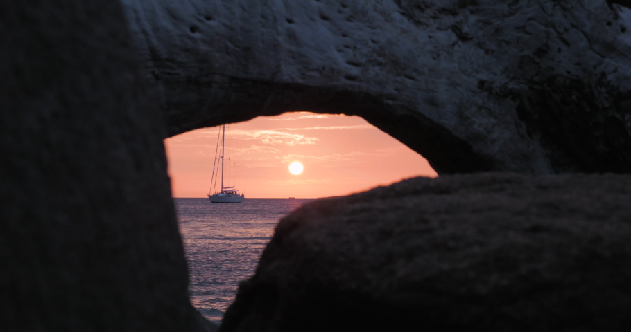 Sunrise at the sea with a beautiful sailing boat in the background, mediterranean sea, corsica island, france