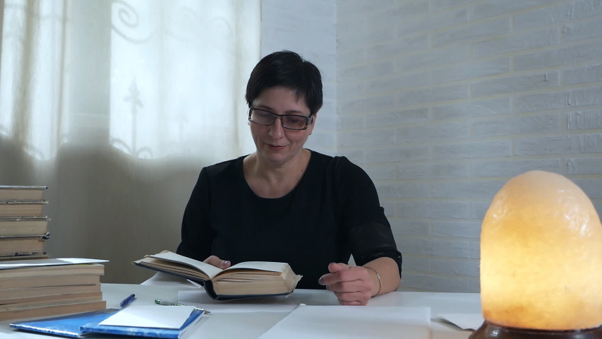 A librarian checks books after readers. Woman leafing through books in the library against the background of a dim lamp. The concept of knowledge. Reading, library, knowledge | Shutterstock HD Video #1038481316