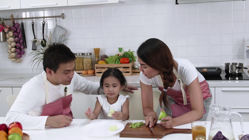 Happy Asian family make a cooking. Father, Mother and Daughter are preparing fruit, green apple in the kitchen at home. Healthy food concept and happy holidays | Shutterstock HD Video #1038491336