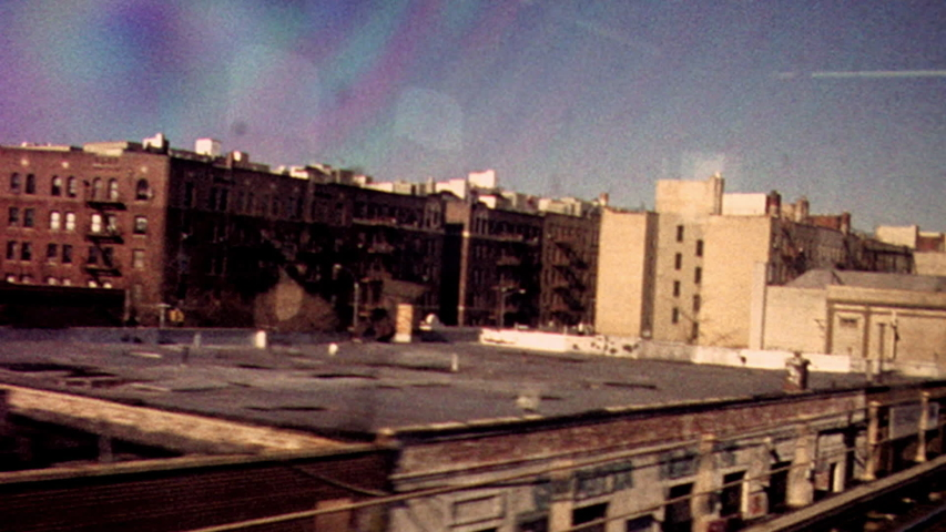 Retro looking archival footage filmed on New York City subway looking out through subway window at tracks and passing train with apartments and graffiti in the distance | Shutterstock HD Video #1038494246