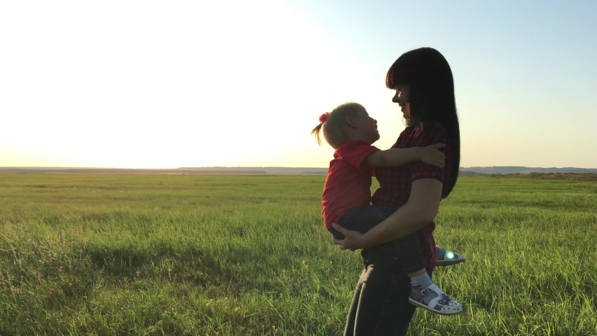 happy family concept a mom and daughter walking carries on hand play outdoors slow motion video. mother are walk carries daughter on walks with her daughter outdoors in the park at sunset playing #1038699896